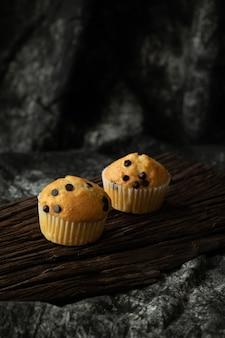 Microprocesadores de chocolate del mollete en el fondo de madera panadería oscura del tono