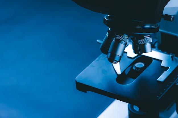 Microscopio científico con lente de metal en el laboratorio.