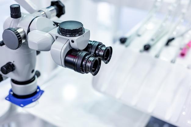 Microscopio dental en el fondo de la odontología moderna. equipo medico. microscopio quirúrgico dental con doble binocular rotativo.