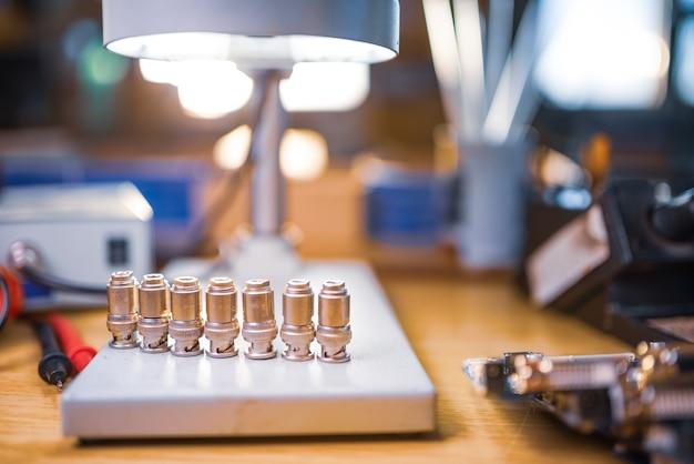 Microscopio electrónico grande y moderno. conector coaxial de microondas y multímetro digital electrónico en mesa de taller. investigación de componentes radioelectrónicos de alta frecuencia en un laboratorio científico