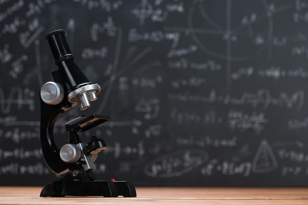 Microscopio escolar sobre una madera y un fondo de pizarra escrito con fórmulas y ecuaciones matemáticas