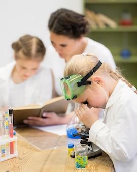 Microscopio y experimentos con chicas jóvenes.