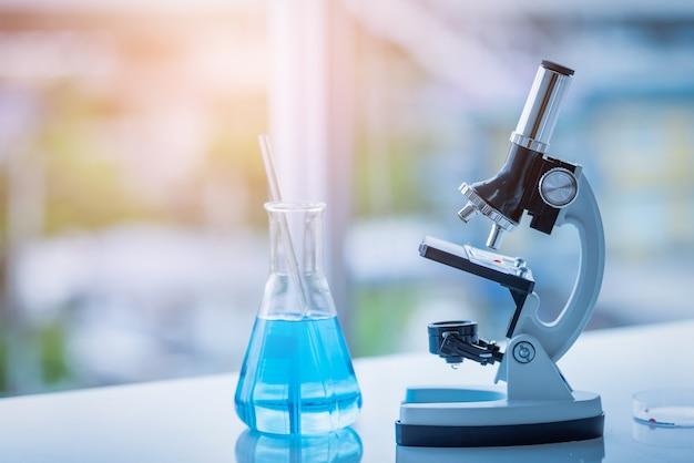 Microscopio y vaso de precipitados en la mesa en el laboratorio