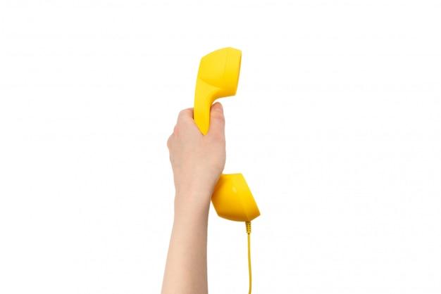 Microteléfono amarillo en la mano de la mujer aislada en blanco.