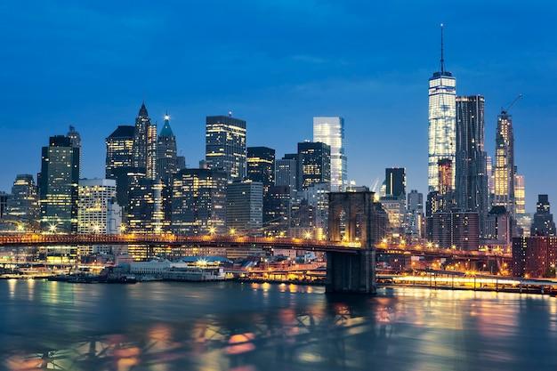 Midtown de manhattan de nueva york al anochecer con el puente de brooklyn. estados unidos.