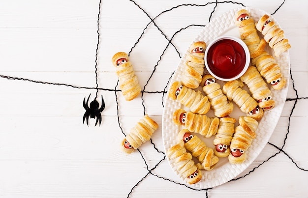 Miedo de salchicha momias en masa con ojos graciosos en la mesa. comida de halloween
