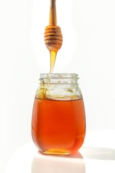 Miel de abeja con una cuchara de madera para miel. aislado
