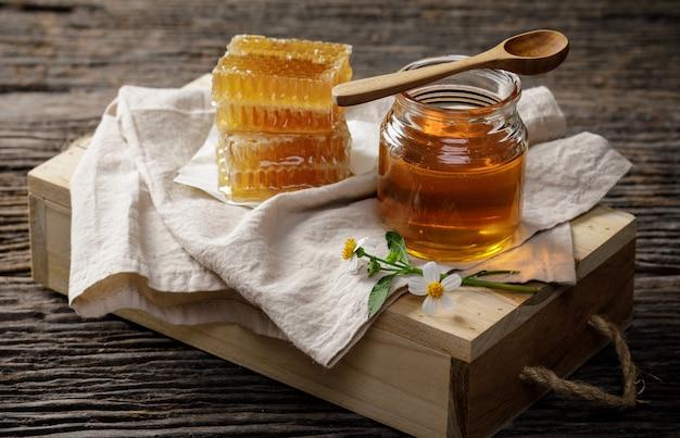 Miel de abeja en tarro y panal con cucharón de miel y flor en mesa de madera