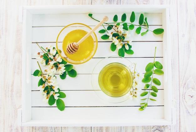 Miel con acacia y té. enfoque selectivo