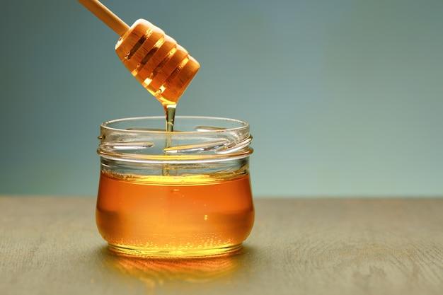 Miel con cucharón de madera sobre mesa de madera