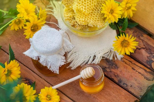 Miel con cucharón de miel en la mesa de madera. miel floral orgánica con flores.