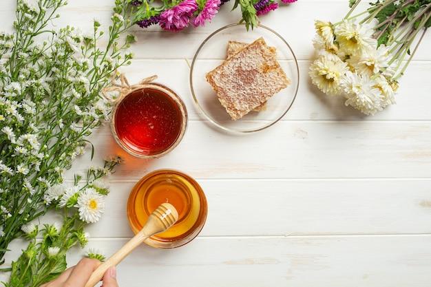 Miel deliciosa sobre superficie de madera blanca