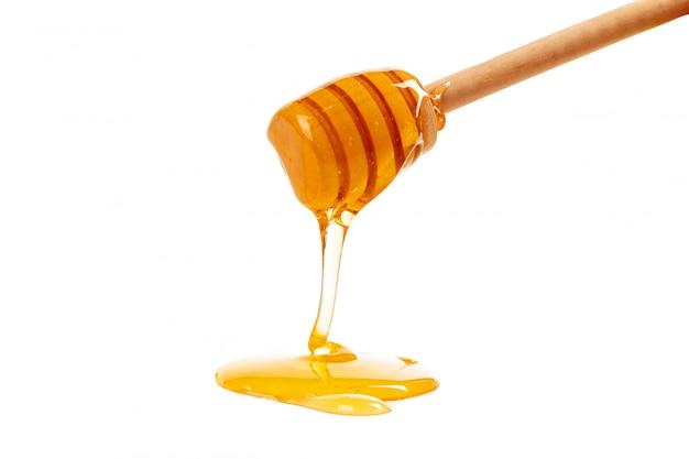 Miel con drizzler de madera aislado en blanco