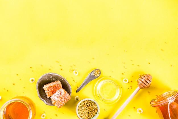 Miel floral orgánica, en frascos, con polen y panales de miel, con flores silvestres, diseño creativo, pared amarilla brillante, vista superior, espacio de copia