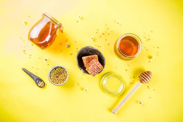Miel floral orgánica, en frascos, con polen y panales de miel, con flores silvestres, diseño creativo, pared amarilla brillante