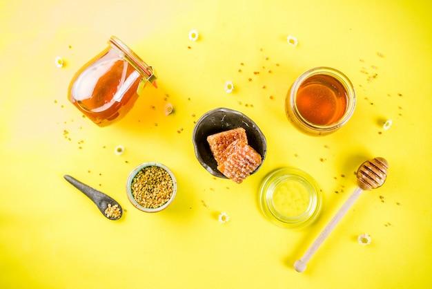 Miel floral orgánica, en frascos, con polen y panales de miel, con flores silvestres, diseño creativo, superficie amarilla brillante, vista superior, espacio de copia