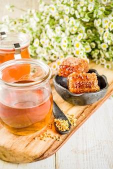 Miel floral orgánica, en frascos, con polen y panales de miel, sobre una mesa de madera blanca, con flores silvestres