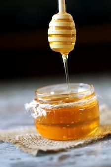 La miel fluye del cucharón de miel.