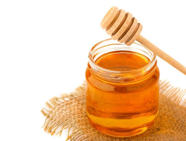 Miel en frasco con una cuchara de madera aislada en blanco