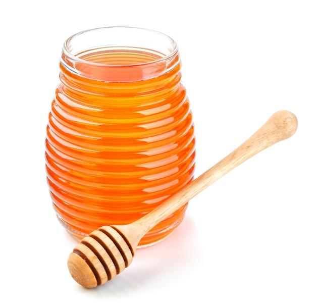 Miel en frasco de vidrio aislado sobre fondo blanco.