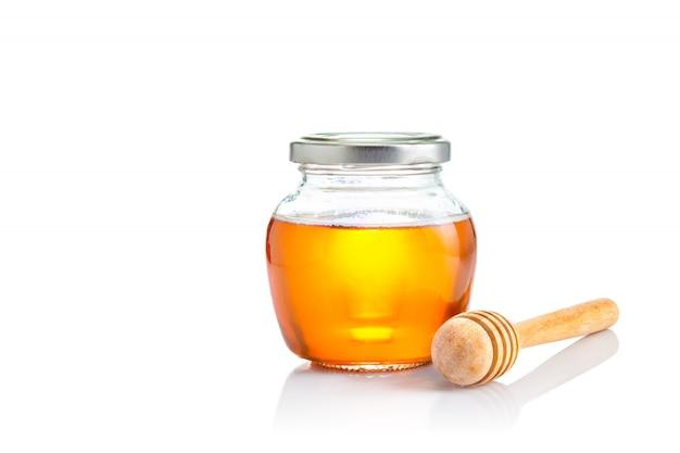 Miel en un frasco de vidrio de tapa cerrada con un cucharón de madera en su lado, todo sobre fondo blanco