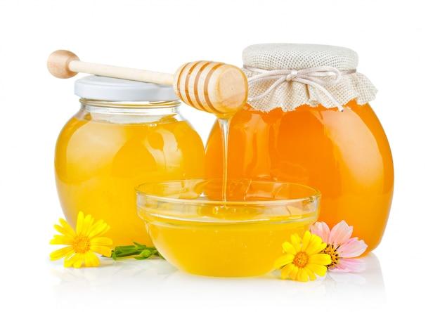 Miel fresca con cucharón y flores aisladas