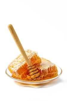 Miel fresca y cucharón de miel aislado, productos de abejas por concepto de ingredientes naturales orgánicos
