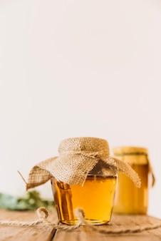 Miel fresca en frasco cerrado sobre superficie de madera