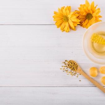 Miel; golosinas; semillas de polen de abeja y flores en superficie de madera