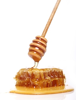 Miel goteando de una cuchara de madera