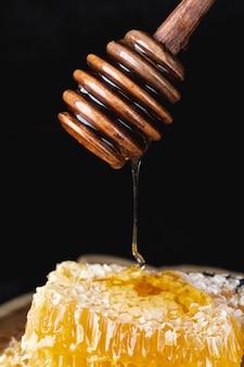 Miel goteando del cucharón sobre honneycomb