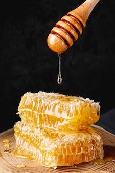 Miel goteando del cucharón sobre honneycombs
