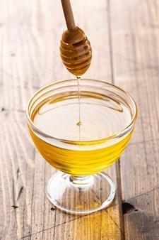Miel goteando del cucharón en vidrio