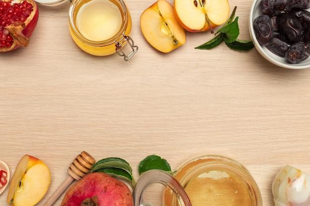 Miel, granada, manzana y dátiles sobre tabla de madera. año nuevo judío rosh hashana celebración