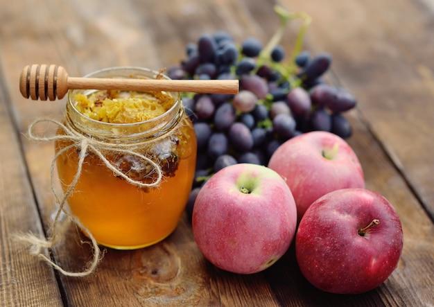 Miel en un hermoso frasco, huso de cuchara de madera, uvas y manzanas en una superficie de madera
