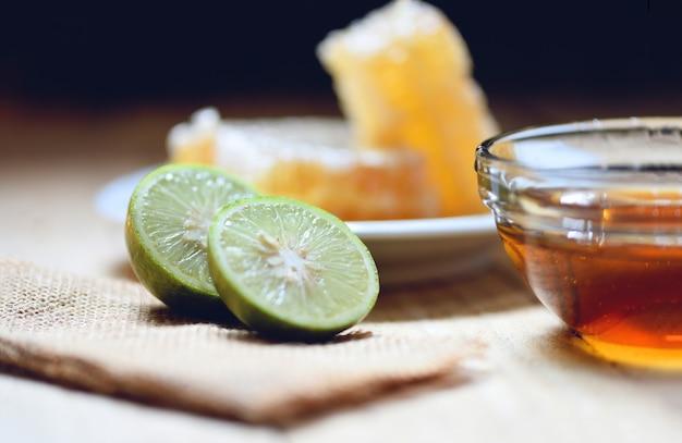 Miel y lima - cerca del panal dulce amarillo en la madera alimentos naturales saludables
