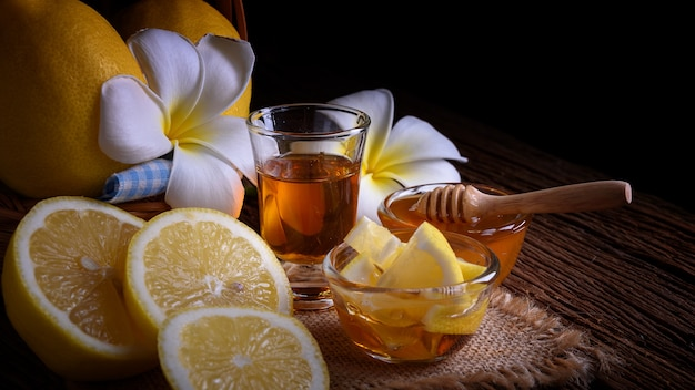 Miel con limones en mesa de madera.