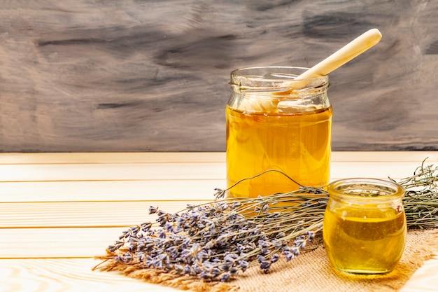 Miel líquida fresca en frascos de vidrio con un cucharón de madera