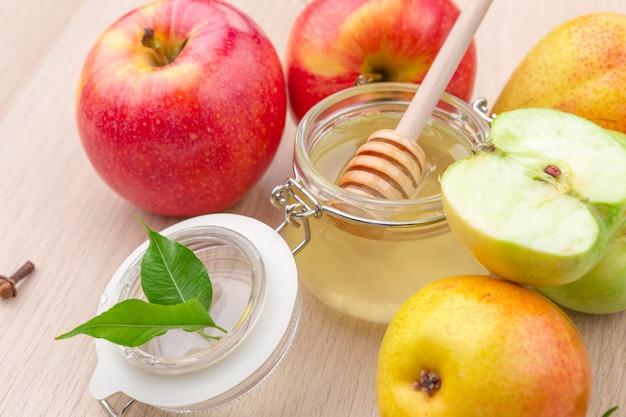 Miel y manzanas en mesa de madera.