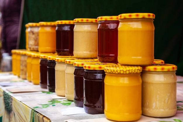 Miel natural en frascos de vidrio en el mercado. tarros con varios tipos de miel pura, cruda y fresca.