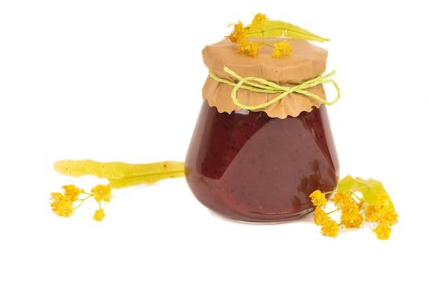 Miel orgánica en frasco de vidrio con flores de tilo, aislado