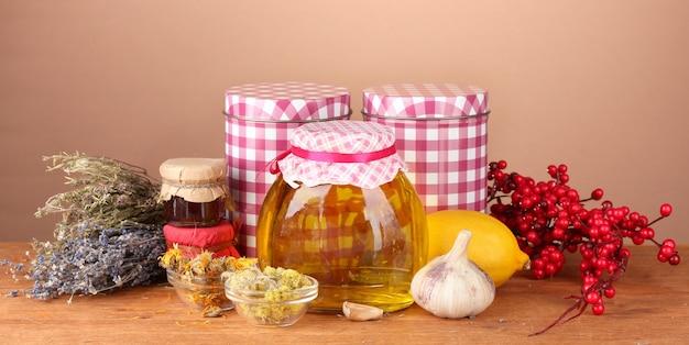 Miel y otras medicinas naturales para la chimenea de invierno, sobre mesa de madera en marrón