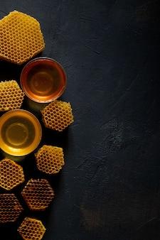 Miel con panal en mesa negra, vista superior. espacio para texto.