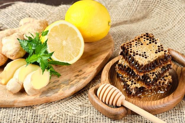 Miel en panales en un plato de madera y miel con nueces con limón y jengibre en estilo rústico en un espacio de madera.