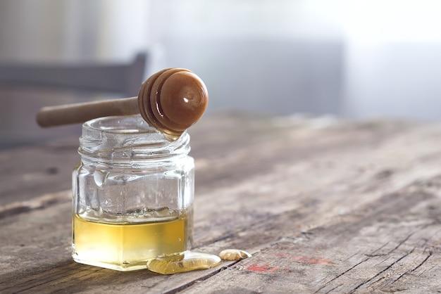 Miel que gotea del cazo en el tarro en la mesa de madera vieja