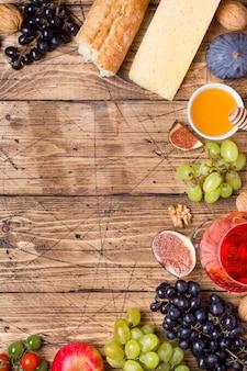 Miel de queso, vino, uvas baguette higos y bocadillos en la mesa de madera rústica con espacio de copia.