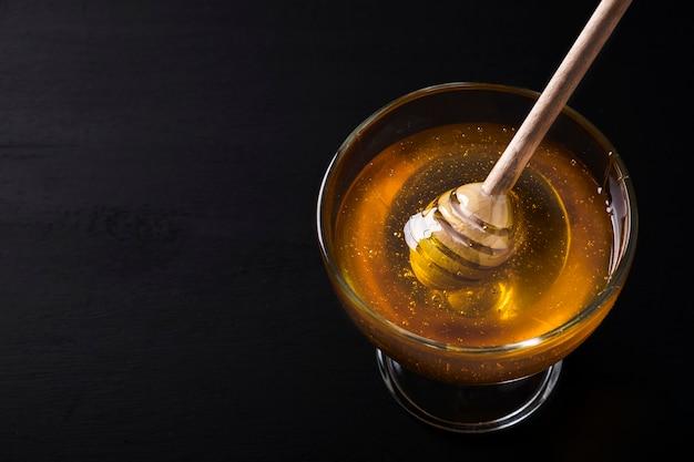 Miel en un recipiente de vidrio cazo de miel sobre un fondo oscuro. espacio para texto.