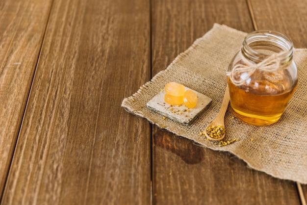Miel; semillas de polen de abeja y caramelos en tela de saco sobre fondo de madera