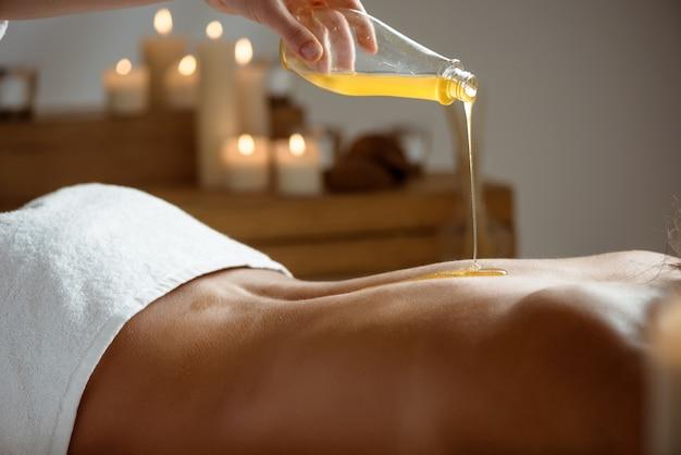 Miel sobre la espalda desnuda de la mujer en el salón de spa.