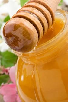 Miel en tarro de cristal y palo de madera con flores.